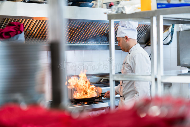 Chef or cook in hotel kitchen cooking dishes royalty free stock photography