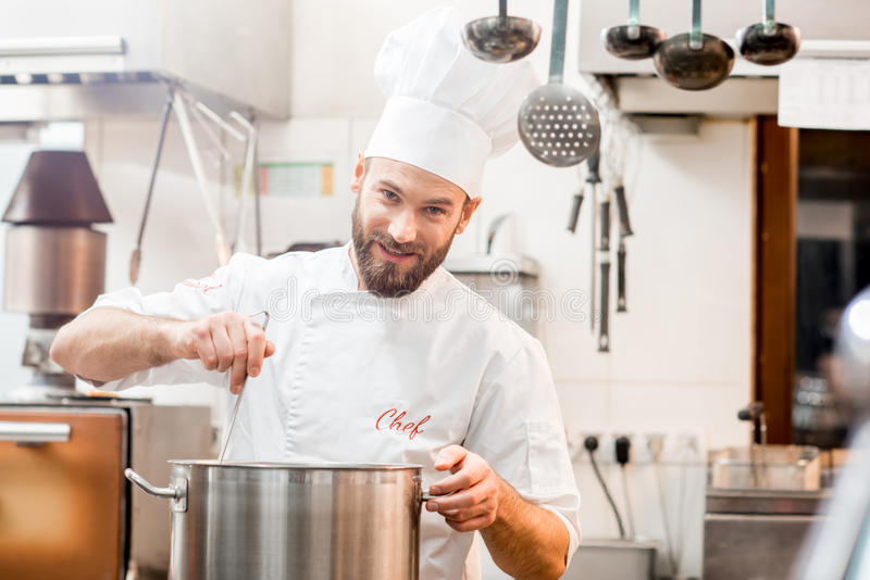 Chef cook at the kitchen. Chef cook in uniform cooking soup in the big cooker at the restaurant kitchen royalty free stock photography