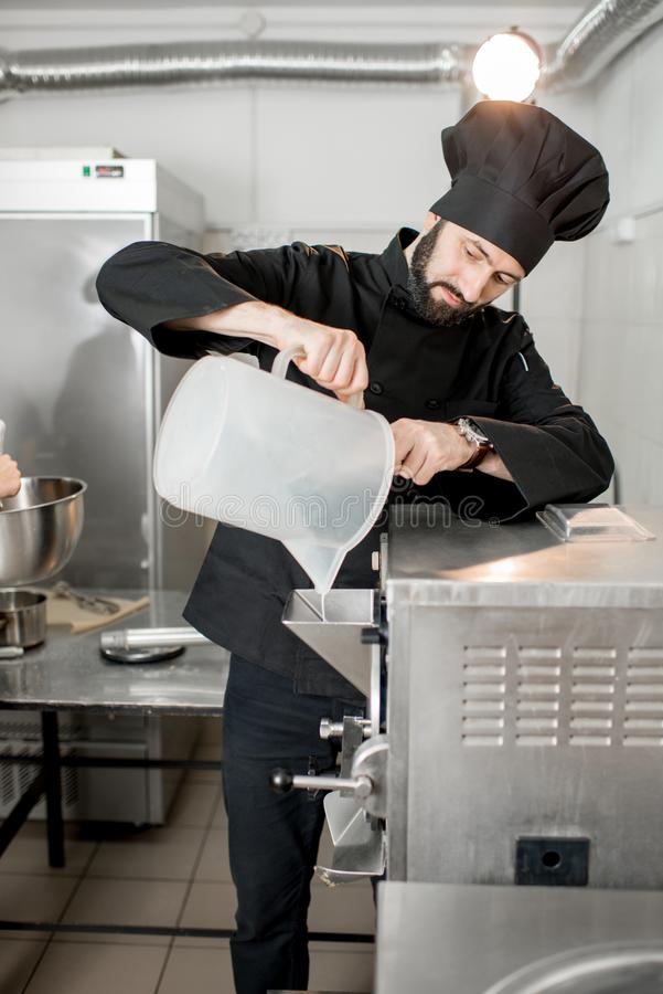 Chef cook making ice cream. Chef pouring basis into the ice cream freezer machine in the small manufacturing stock photos