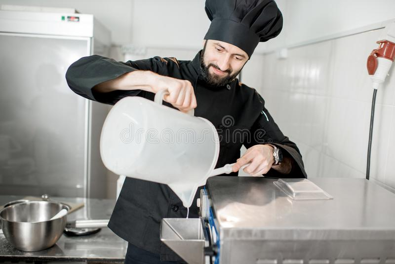 Chef cook making ice cream. Chef pouring basis into the ice cream freezer machine in the small manufacturing stock image