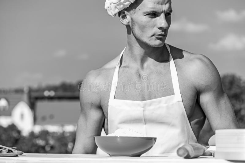 Chef cook with nude muscular torso. Man on confident face wears cooking hat and apron, skyline on background. Cook. Or chef with muscular shoulders and chest royalty free stock image