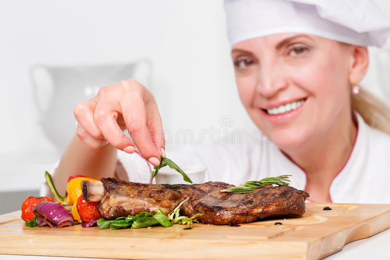 Chef-cook presenting meals. Close-up with selective focus on rosemary leaf which a cook is putting on meat steak royalty free stock photo