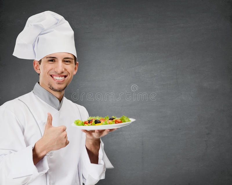 Chef cook with vegetable salad dish thumbs up. Grey background stock photography