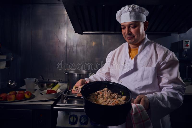 Chef cook in a white apron and cooks hat on a kitchen royalty free stock photos