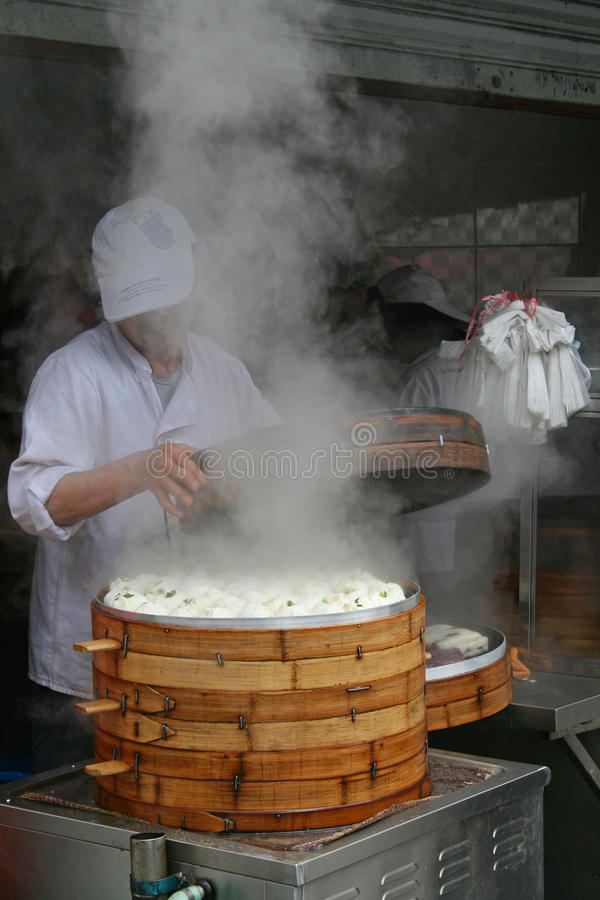 A Chef cooking Baozi in a bamboo steamer at a street food stall royalty free stock photos