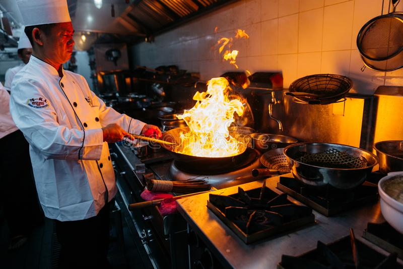 Chef cooking Chinese food with burning fire on steel pan.  royalty free stock photos