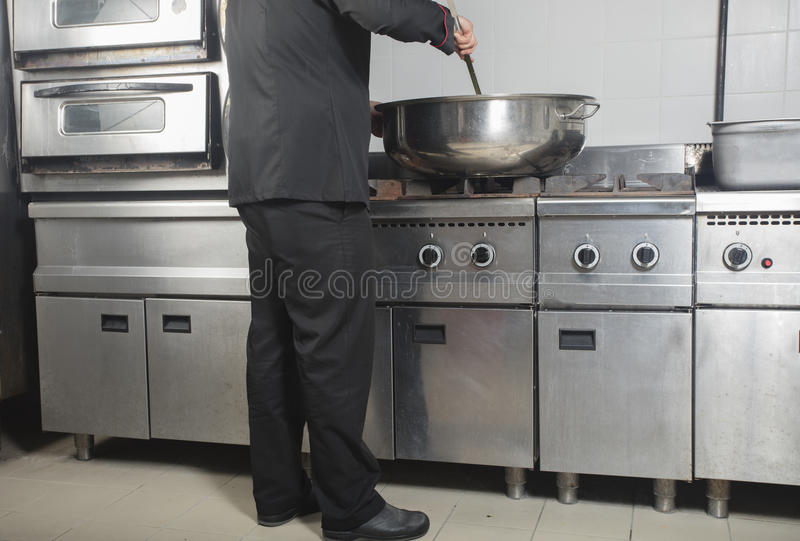 Chef cooking at commercial kitchen royalty free stock image