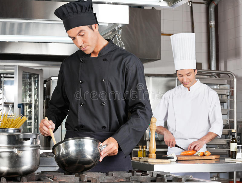Chef-Cooking Food With-Kollege-Hacken lizenzfreie stockfotografie
