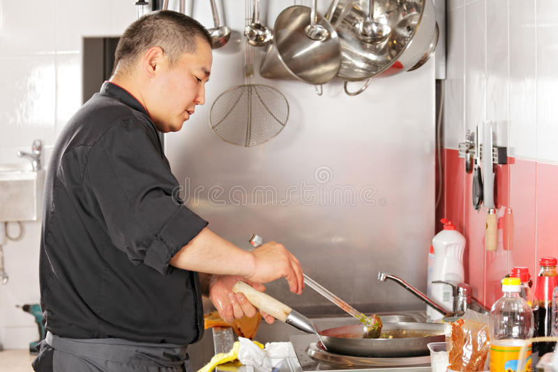 Chef cooking food in wok pan. At the kitchen stock images