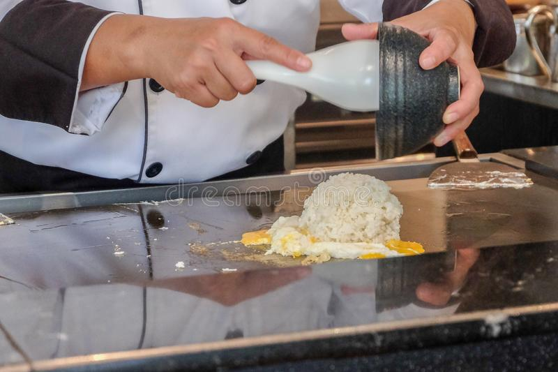 Chef cooking with egg in the kitchen royalty free stock photography