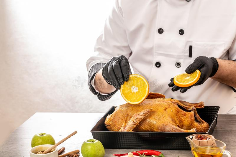 Chef cooking meat duck with oranges and apples on kitchen white background. Hotel service and restaurant food concept. copy text royalty free stock photo