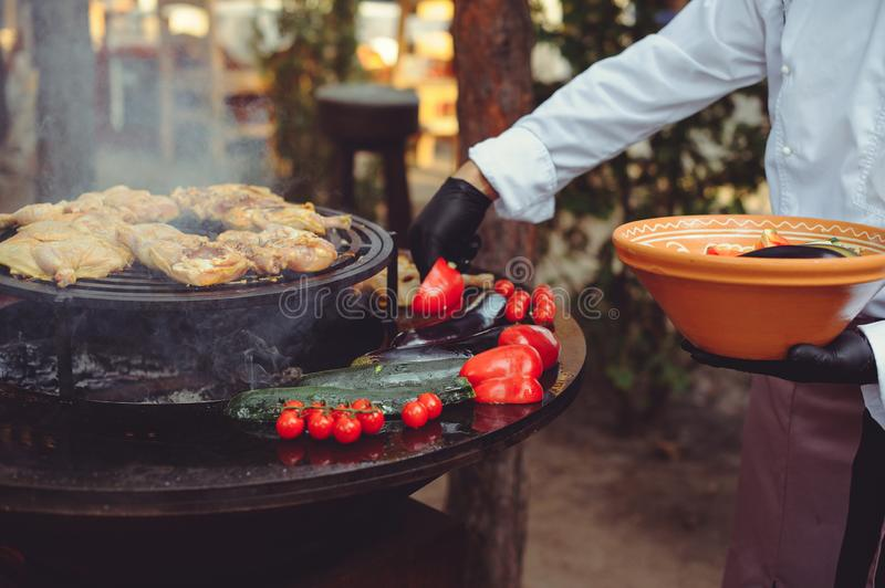 The chef is cooking meat on the grill. Golden rib steaks and chicken with grilled vegetables, delicious food royalty free stock photos
