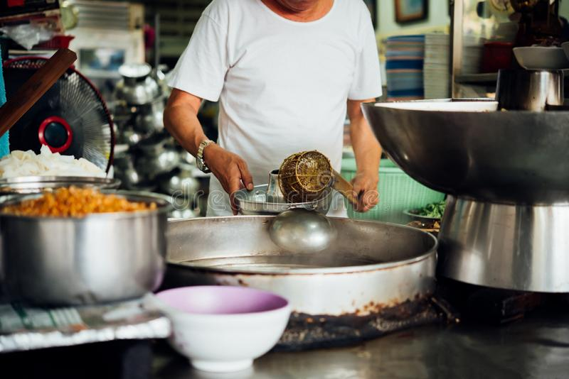 Chef cooking a noodle soup at street food market. Asian chef cooking a noodle soup with meat ball kauy-tiew for sale at Thai street food market or restaurant in stock image