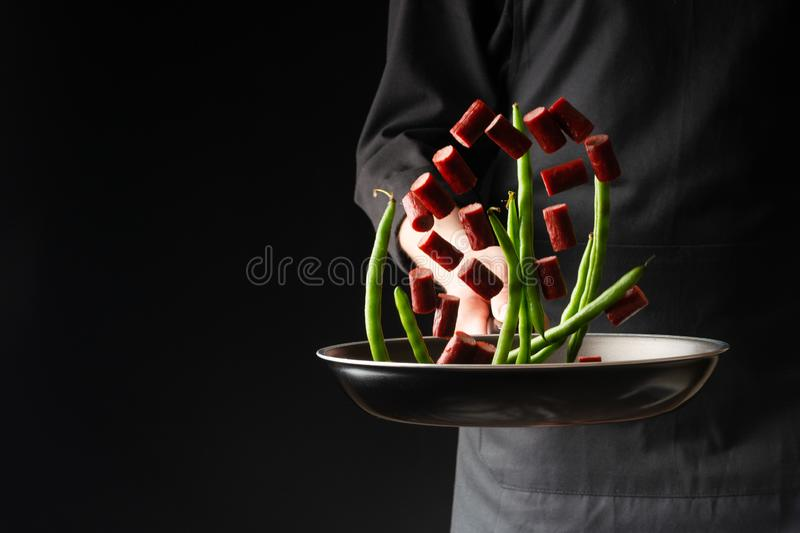Chef is cooking pepperoni sausages with green beans, on a black background, a recipe book, German sausages.  stock images