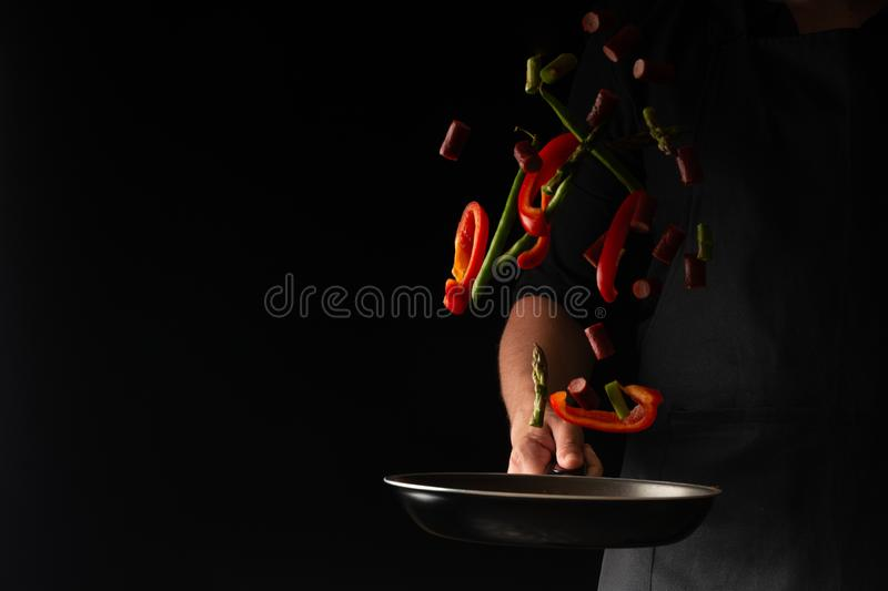 Chef is cooking pepperoni sausages with sweet pepper and spriykovoy beans, on a black background, a recipe book, German sausages.  stock photos