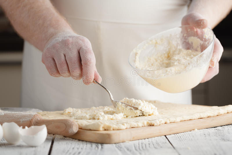 Chef cooking preparing cottage cheese pancakes on a wooden boa royalty free stock photography