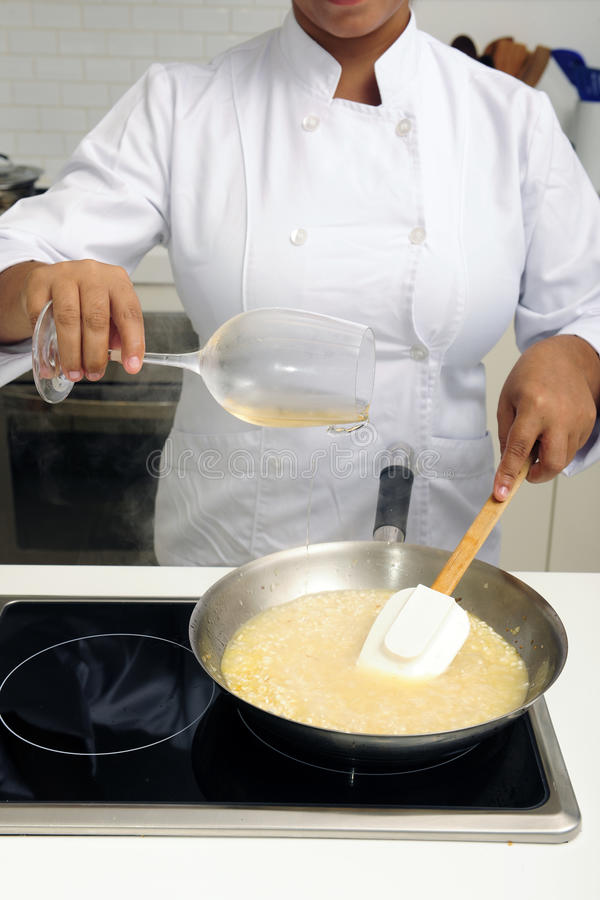 Chef cooking risotto pouring wine stock photo