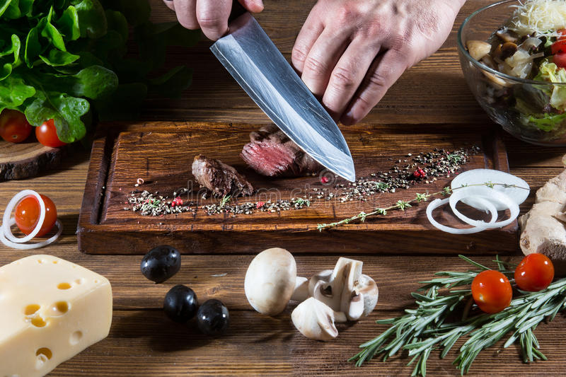 Chef cooking steak close-up royalty free stock images
