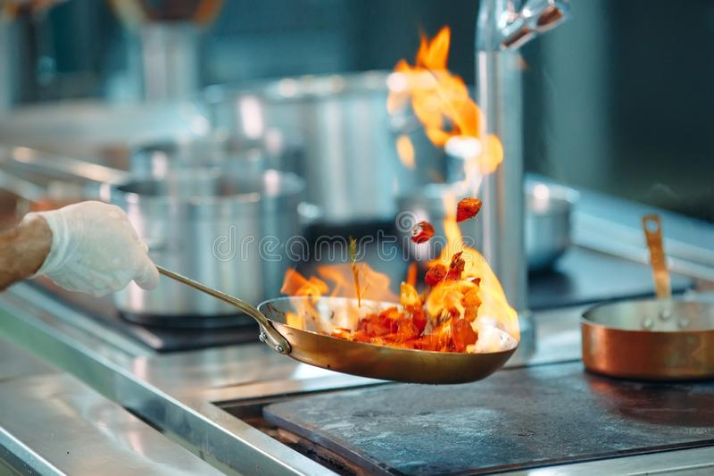 Chef cooking vegetables in wok pan. Shallow dof. stock image