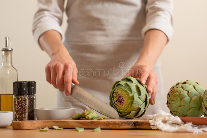 Chef cooks artichoke y slicing it on a light background, concept cooking tasty and healthy food, menu, recipe book, detox,. Restaurants royalty free stock photography