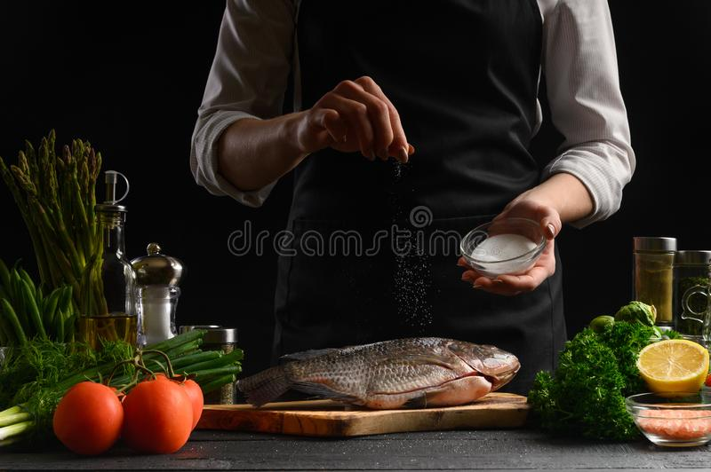 Chef cooks fresh fish on the background with ingredients, salts it before cooking, freezing in motion, advertising photo for. Seafood sale, cookbook for recipes stock images