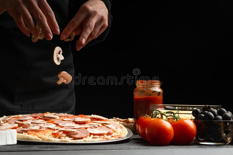 Chef cooks Italian pizza, sprinkles with mushrooms. Freeze in motion. Against the background of pizza ingredients. Black. Background with space for design stock photography