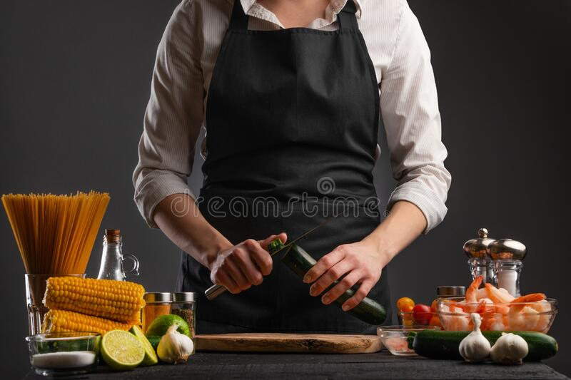 Chef cooks Shrimp Stir Fry, peel zucchini. Seafood. Against the background of ingredients. Asian cuisine, Oriental food. Culinary. Background, recipe book, home royalty free stock photos