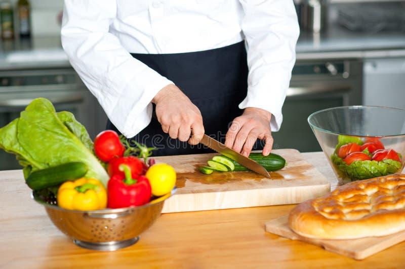 Chef coupant des légumes images stock