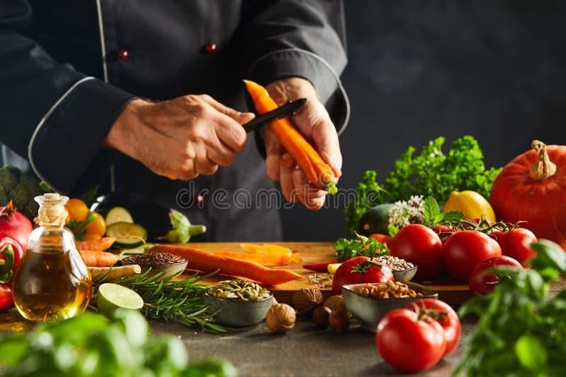 Chef coupant en tranches les carottes fraîches pour une salade images libres de droits