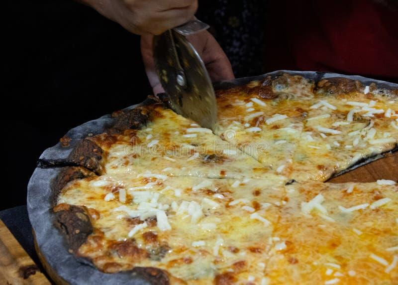 Chef coupant la pizza fraîchement cuite au four, pizza préparée faite maison photo libre de droits