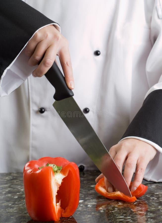 Chef coupant le poivron rouge images libres de droits