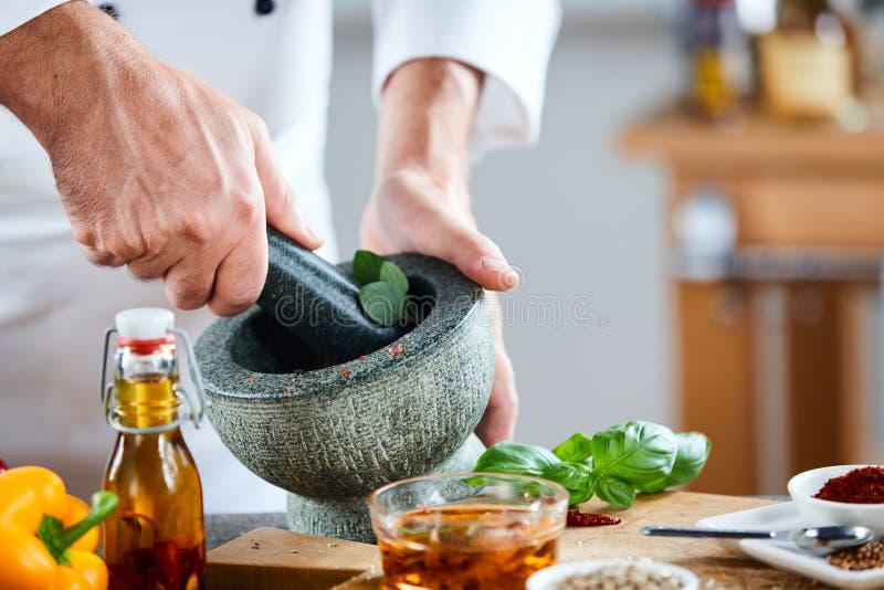 Chef crushing a blending fresh herbs royalty free stock photos