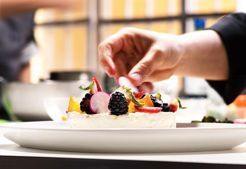Chef in cuisine prepars cheesecake with fruits. Chef in cuisine prepars cheesecake stock photography