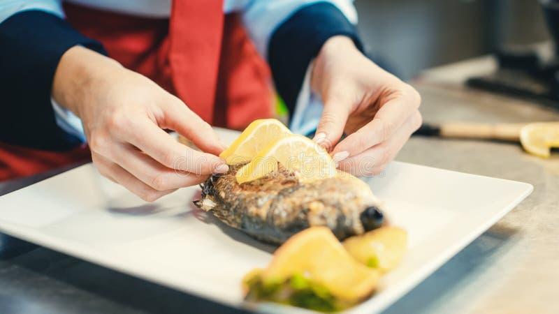Chef cuisinier du restaurant mettant de la nourriture sur un plat qui sera bientôt servi photo libre de droits