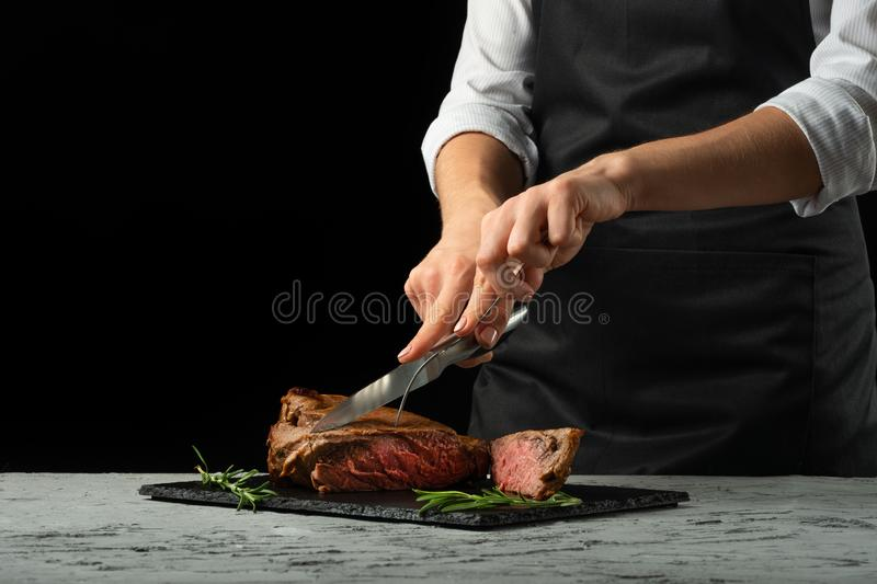 Chef, cut with a meat steak on a black background with an open space for text or restaurant menus. Horizontal photo Black text are royalty free stock image