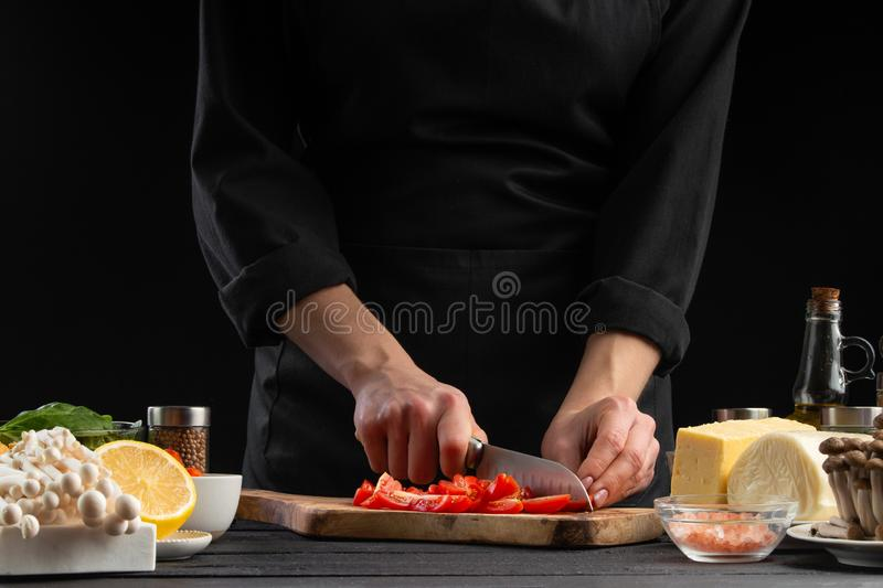 The chef cuts cherry tomatoes to prepare a tasty and fresh salad. Vegetarian and fresh food, gastronomy and cooking, recipe book. And recipes. On a black stock image