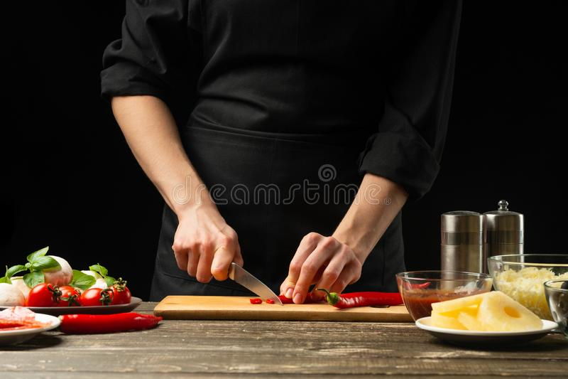 The chef cuts hot chilli peppers. For the preparation of pizza, salad. A delicious and spicy food concept, Mexican, cooking. On a royalty free stock photo