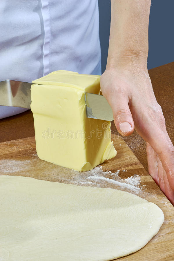 Chef cuts a large piece of butter spread on the dough preparation cheesecakes series full cooking food recipes royalty free stock image