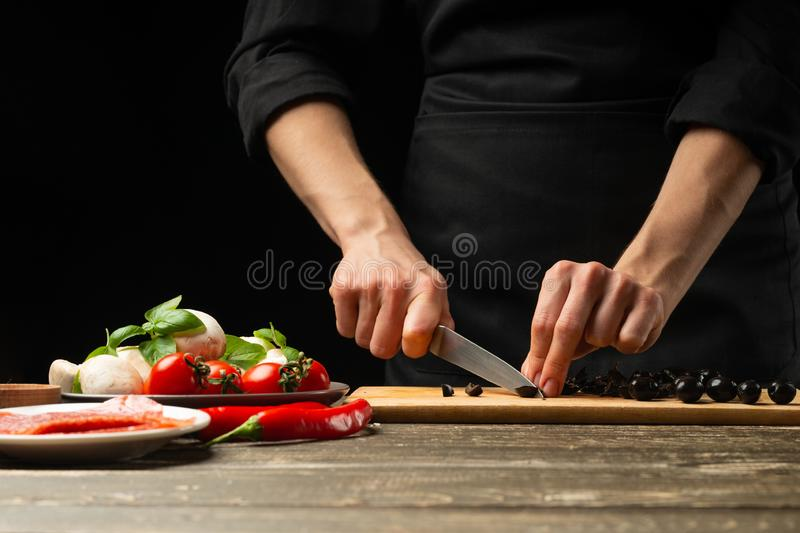 The chef cuts the olives. For the preparation of pizza, salad. A delicious meal concept. On a black background for design or. Lettering text stock photography