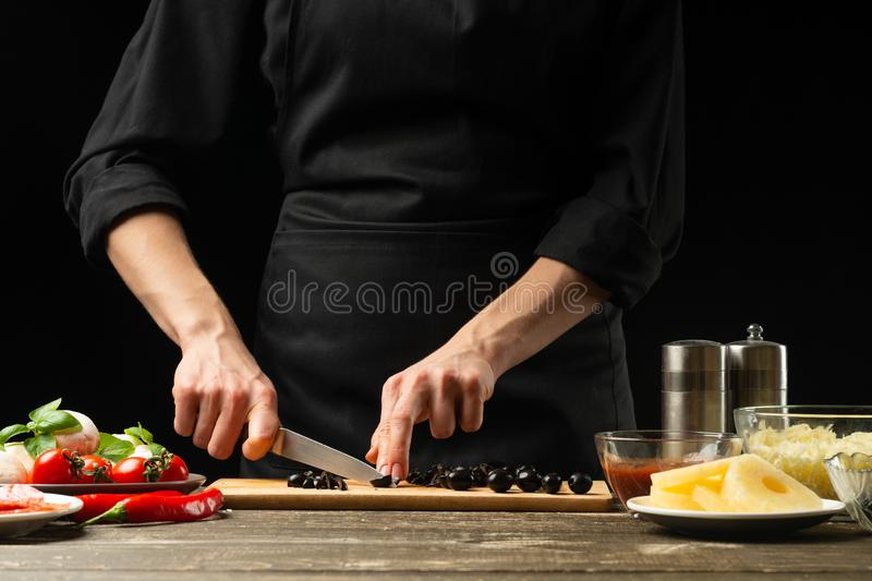The chef cuts the olives. For the preparation of pizza, salad. A delicious meal concept. On a black background for design or. Lettering text royalty free stock photo