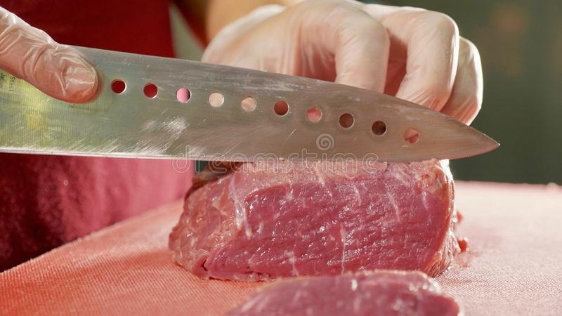 The chef cuts raw meat with the knife on red board, closeup. The professional chef in gloves cuts raw meat with the knife on red board at commercial kitchen royalty free stock photography