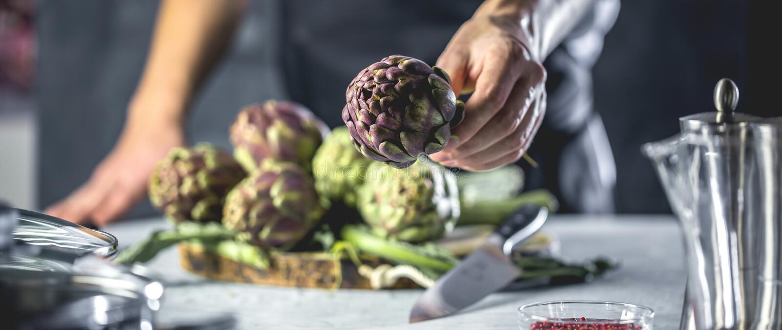 Chef cutting artichokes for dinner preparation - Man cooking inside restaurant kitchen royalty free stock images