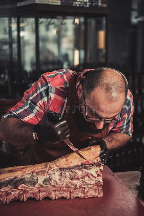 Chef cutting beef carcass in a restaurant.  royalty free stock images