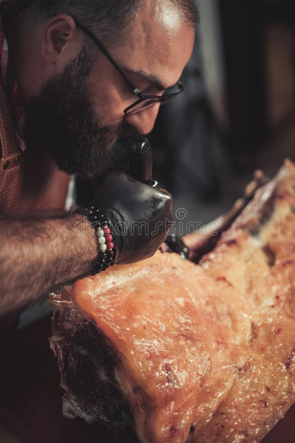 Chef cutting beef carcass in a restaurant.  royalty free stock image