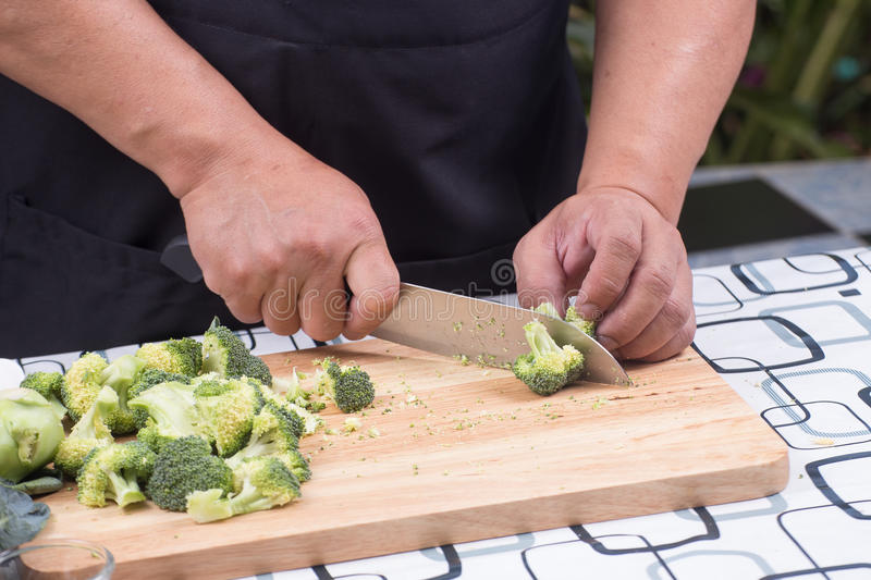 Chef cutting broccoli for cooking. / Stir fry broccoli concept royalty free stock image