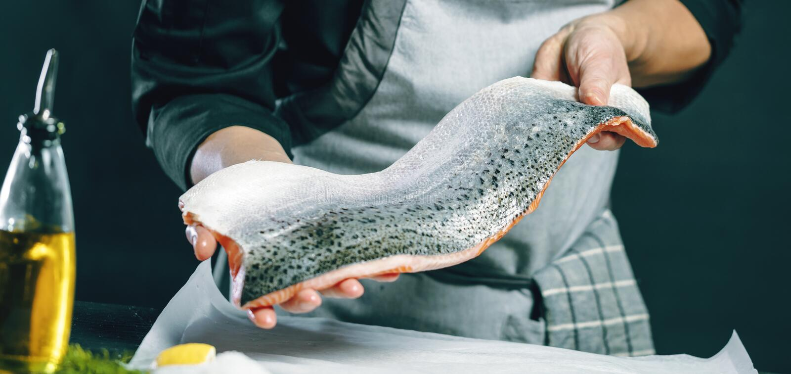 Chef cutting and cooking big salmon in a restaurant kitchen royalty free stock photography