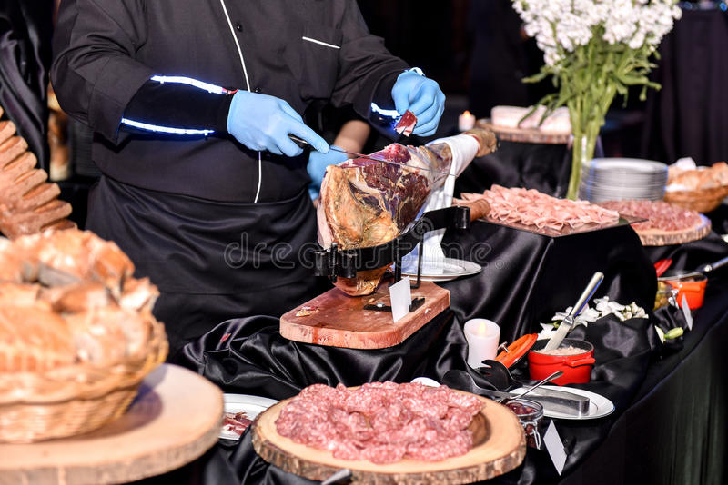 Chef cutting ham in night event. royalty free stock images