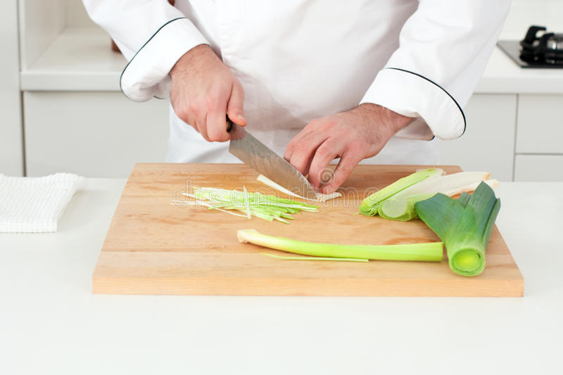 Chef cutting leek. With julienne technique stock photo