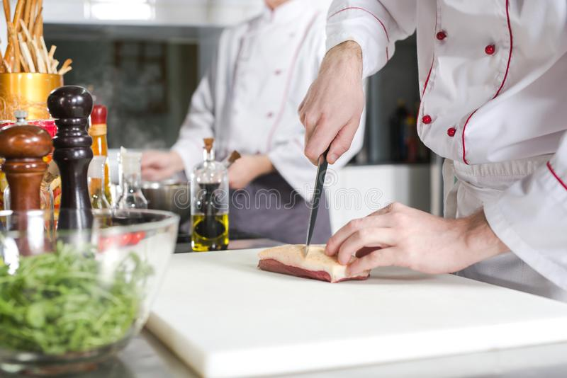 Chef cutting meat on chopping board, professional cook holding knife and cutting meat in restaurant. Chef cutting meat on chopping board, professional cook royalty free stock photo
