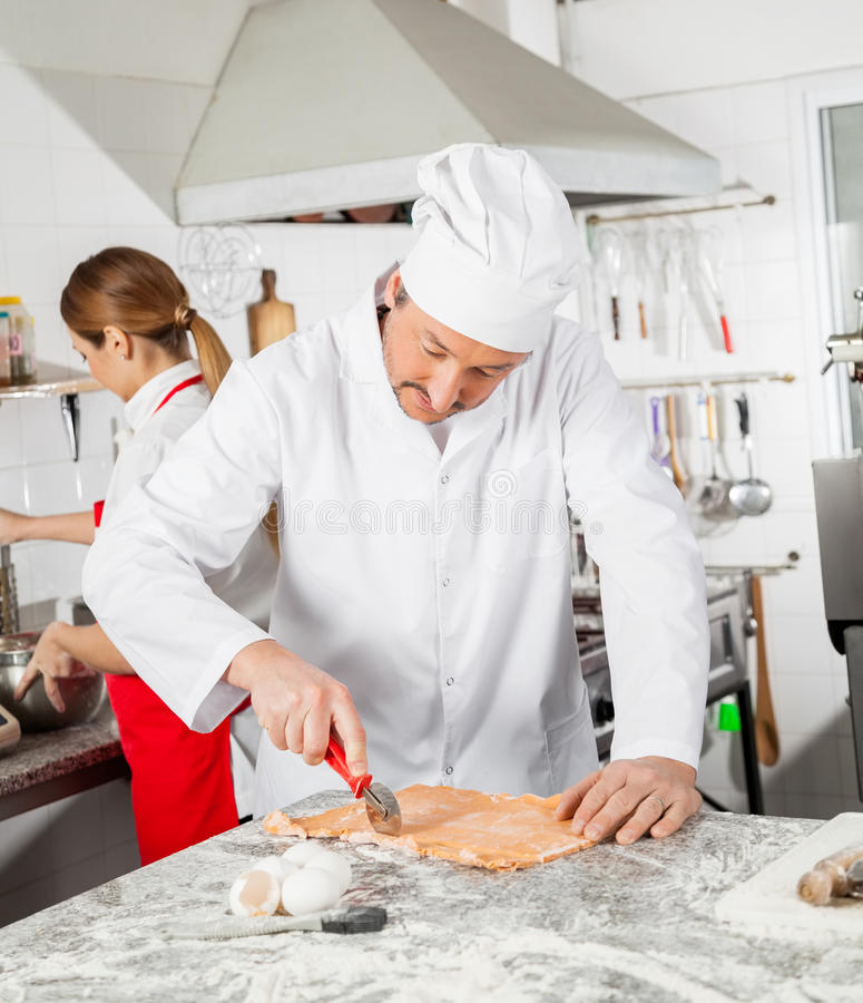 Chef Cutting Ravioli Pasta With Colleague Working stock photos